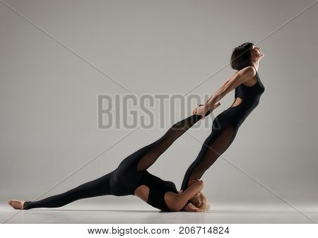 Portrait of young acrobatic female pair doing hard pose