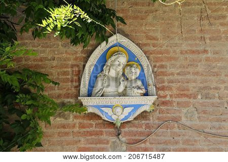 Grazzano Visconti Italy - August 07 2016: Wall bas-relief of the Madonna and Child