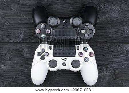 Sankt-Petersburg Russia September 24 2017: Sony PlayStation 4 Slim 1Tb revision and 2 dualshock game controller on the wooden table background. Home video game console