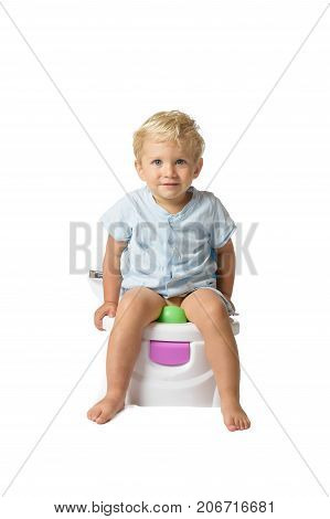 Baby boy white caucasian smiling and sitting on the potty with white background.