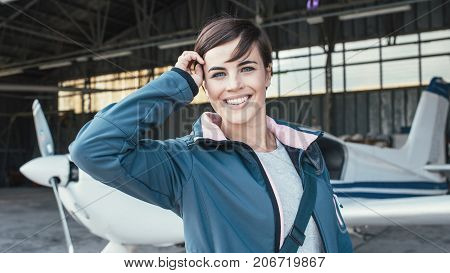 Smiling Young Pilot Posing With A Propeller Plane