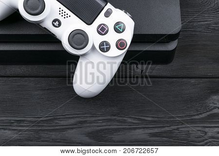 Sankt-Petersburg Russia September 24 2017: Sony PlayStation 4 Slim 1Tb revision and dualshock game controller on the wooden table background. Home video game console