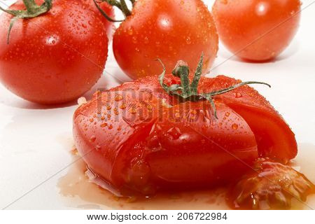 squeezed wet tomato with water drops on white background