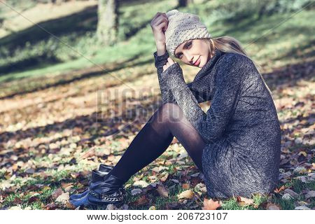 Young Blonde Woman Sitting In A Park With Autumn Colors