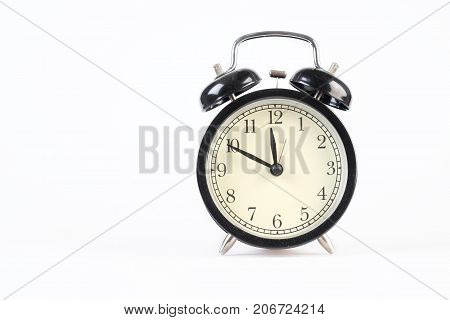 Analog clock telling time at ten to twelve o'clock on white background