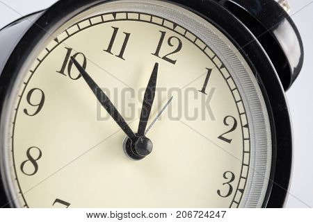Analog clock telling time at ten to twelve o'clock
