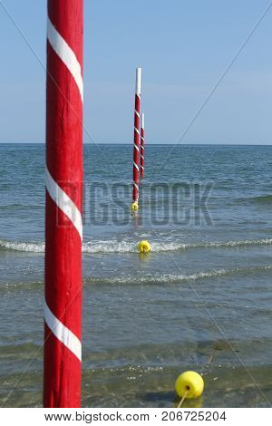 White And Red Poles On The Sea