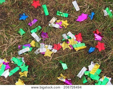 Multi-colored candy wrappers are scattered on a green grass