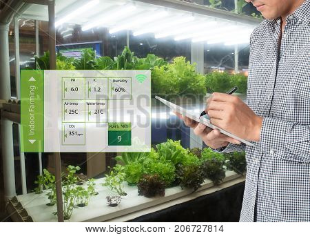 smart agriculture in futuristic concept farmer use technology to monitor control and adjustment led atmospherehumidity water level and keep tracking harvesting time in vertical or indoor farming