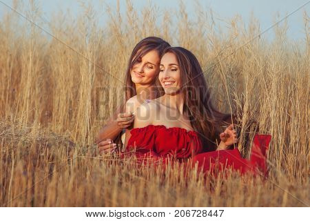 In the field among the tall grass two women flirt.