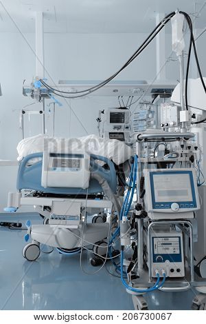 Hospital bed surrounded by a mass of medical equipment.