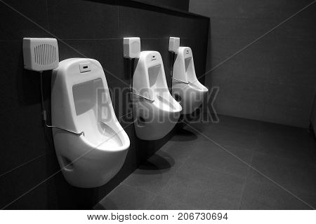 Urinals in the men public restroom with automatic water flushing machine