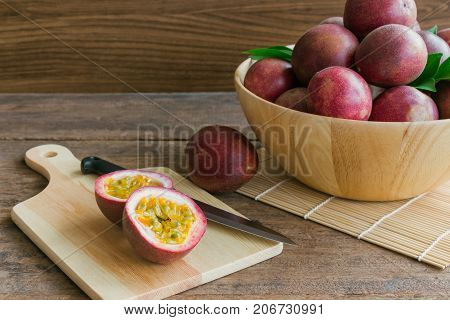 Passion fruit on wood bowl put on wood table in side view for background or wallpaper. Prepare passion fruit on cutting board for homemade dessert or cooking. Ripe passion fruit so sweet and sour. Cutting a half of fresh passion fruit.