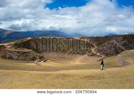 Tourist Exploring The Archaeological Site At Moray, Travel Destination In Cusco Region And The Sacre
