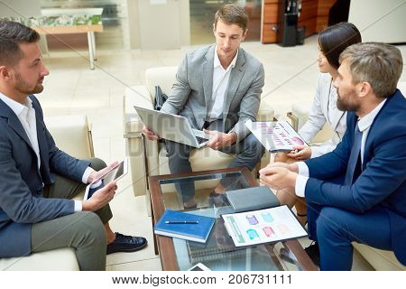 Group of confident financial managers in formalwear gathered together at spacious boardroom and analyzing statistic data with help of laptop, printed diagrams and graphs