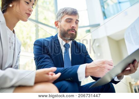 Low angle view of concentrated white collar workers analyzing results of accomplished work while having working meeting at spacious office lobby with panoramic windows