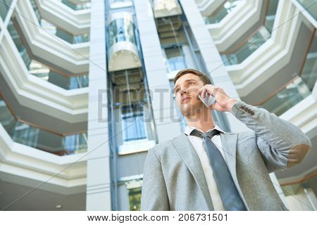 Low angle view of confident young businessman talking to his colleague on smartphone while standing at spacious office lobby, waist-up portrait shot