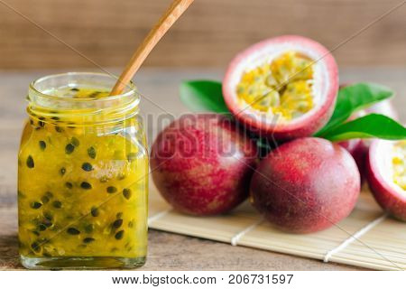 Homemade delicious passion fruit jam in bottle put on wood table. Fresh passion fruit and homemade jam on wood table in natural tone style concept. Close up bottle of passion fruit jammacro concept. Passion fruit jam ready to served.
