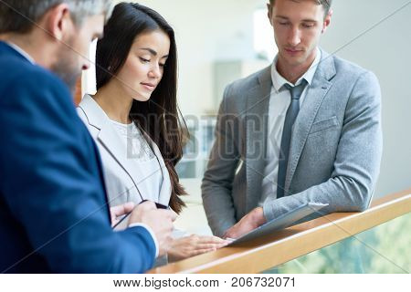 Pretty young white collar worker with clipboard in hands sharing creative ideas with male colleagues while having informal meeting at office lobby