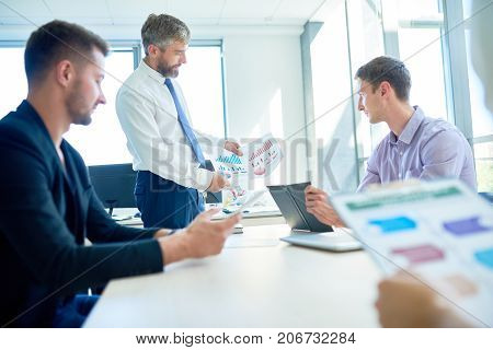 Hard-working team of managers analyzing role of their department in company productivity while having working meeting at spacious boardroom