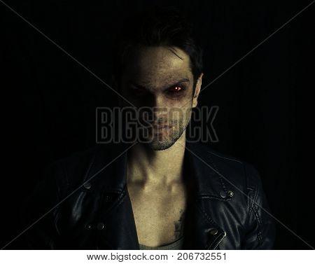 Dark vampire posing on a black background