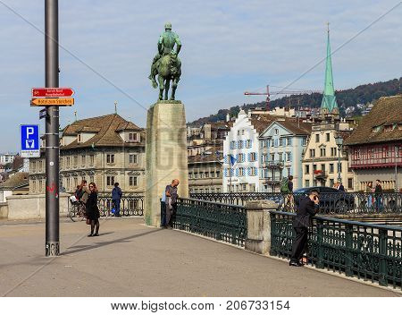 Zurich, Switzerland - 29 September, 2017: buildings of city's old town along the Limmat river, the monument to Hans Waldmann, people on Munsterbrucke bridge, Zurich Town Hall building in the background. Zurich is the largest city in Switzerland.
