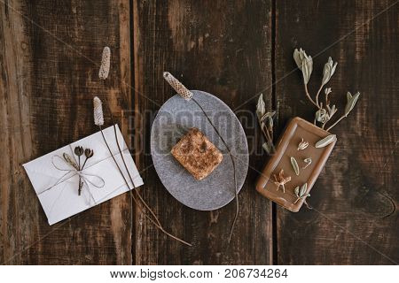 Top view of still life with handmade organic rustic soap with dried flowers soap-dish and little white cute romantic envelope on dark wooden table background.