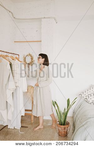 Attractive brunette young woman in glasses and linen beige robe at home standing in her white room in morning in front of rail with clothes and chooses outfit for day.