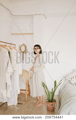 Attractive brunette young woman wears glasses and linen beige robe at home standing in her white room in front of rail with clothes in morning.