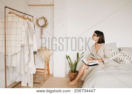 Young pretty lady with short black hair sits on bed in morning in her big white room and looks on her wardrobe holding opened book and wearing glasses and linen beige robe. Space for text.