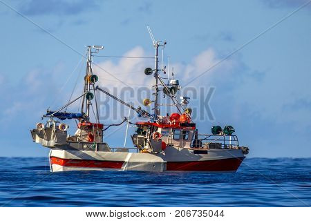 Sustainable Commercial mackerel hook line fishing vessel on blue waters of Norwegian fjord