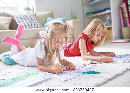 Portrait of two little girls coloring pictures together lying on floor on thick plush carpet in cozy living room at home