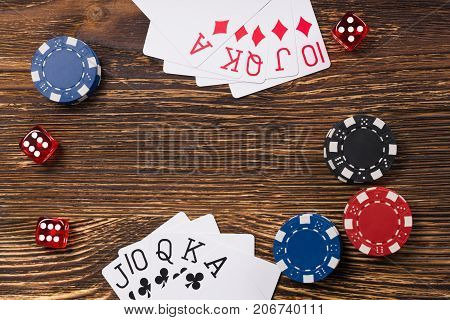 poker game on a wooden table cards with chips and dice of poker