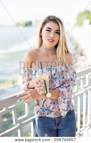 Portrait Of Young Woman Sitting On Promenade And Sight Seeings As Background