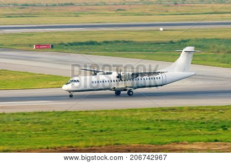 A turboprop passenger plane lands on the runway at the airport the reverse