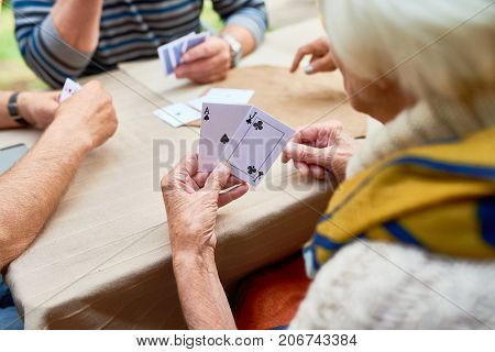 Close-up shot of unrecognizable senior woman playing poker with friends while sitting at outdoor cafe table, over shoulder view