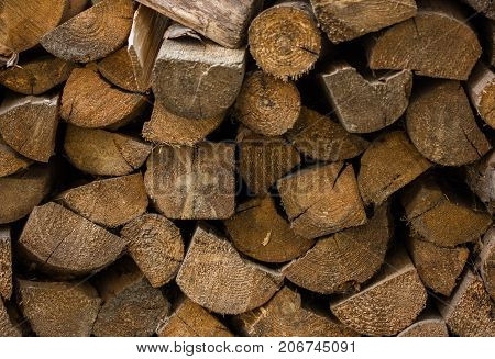 Pile of stacked triangle firewood prepared for fireplace and boiler. Background with pile of firewoods. Closeup of firewoods in the yard - pile of chopped firewood prepared for heating