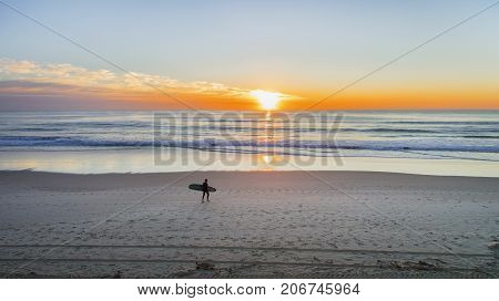 Beach aerial overlooking a surfer walking on the beach with a colorful sunrise over the ocean.