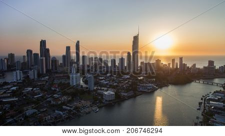 Colourful sunrise views over the ocean, aerial view over Paradise Island towards Surfers Paradise cityscape and the Q1 building