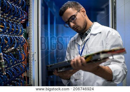 Portrait of young scientist wearing lab coat holding blade server while working with supercomputer in research center