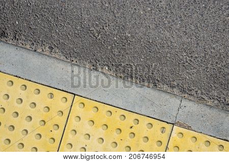 Adjoining Pavement with a Tactile Tile for Blind Peoples and an Asphalt Road. Joint of Road Surfaces Texture