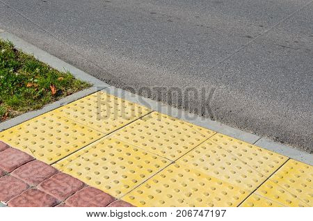 Adjoining Pavement with a Tactile Tile for Blind Peoples and an Asphalt Road. Joint of Road Surfaces