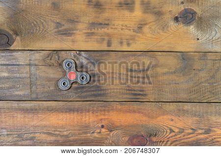 A Rare Handmade Wooden Fidget Spinner Lies On A Brown Wooden Background Surface. Trendy Stress Relie