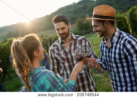 Wine grower family tasting wine in winery vineyard