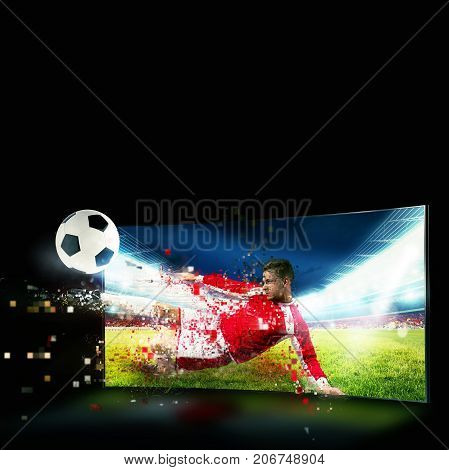 Soccer player comes out of the tv to kick the ball