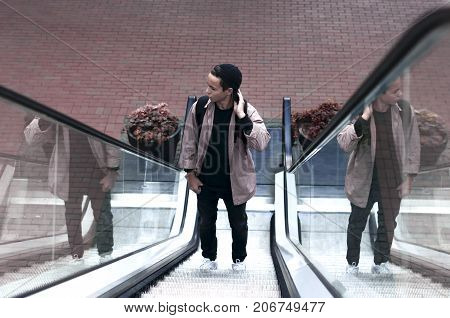 young man standing on an escalator rises up
