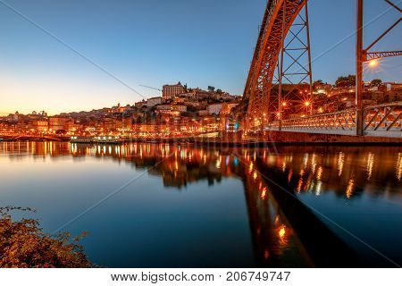 Iconic symbol of Oporto city. Bottom view of scenic iron arch bridge Dom Luis I reflecting on Douro River at twilight in Porto, Portugal's second largest city. icturesque urban evening skyline.