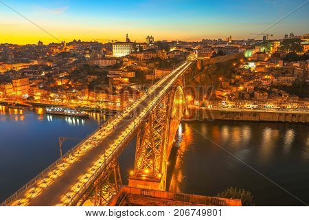 Panoramic aerial view of iron arch bridge Dom Luis I on Douro River at sunset twilight in Porto, Portugal's second largest city. Urban night skyline. Iconic symbol of Oporto city.