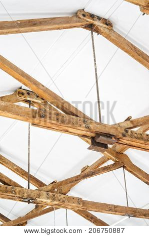Wooden Roof Structure in White Bright Interior. Old Rafters in the Loft Interior