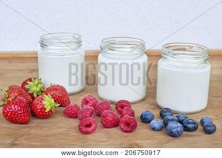 Three glass jars with yogurt and variation of berries